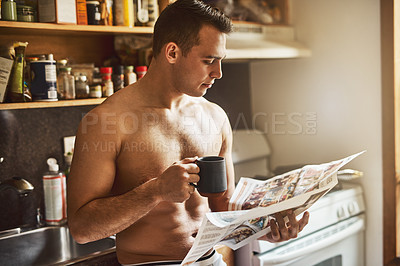 Buy stock photo Cropped shot of a handsome young shirtless man drinking a cup of coffee and reading the newspaper in the kitchen at home