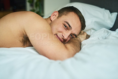 Buy stock photo Cropped shot of a young handsome man lying in bed at home