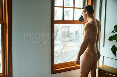 Buy stock photo Cropped shot of a handsome young shirtless man looking out the window while drinking coffee at home