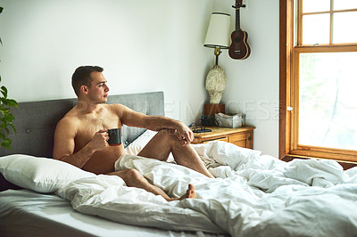 Buy stock photo Shot of a young handsome shirtless man drinking coffee and chilling in bed at home