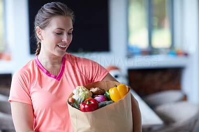 Buy stock photo Cropped shot of a young attractive woman carrying a bag of groceries at home