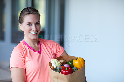 Buy stock photo Portrait of a young attractive woman carrying a bag of groceries at home