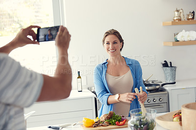 Buy stock photo Cropped shot of an unrecognizable man taking a picture of his wife while she is cooking in the kitchen at home