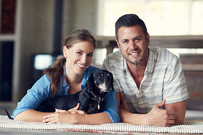 Buy stock photo Portrait of a young married couple spending the day with their pet at home