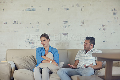 Buy stock photo Cropped shot of a young married couple having a disagreement in the living room at home