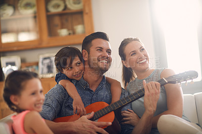 Buy stock photo Shot of a happy father playing the guitar for his family