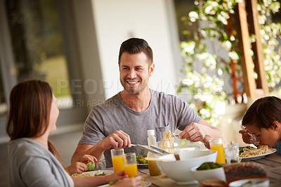 Buy stock photo Cropped shot of a family of three sitting down for a meal at home
