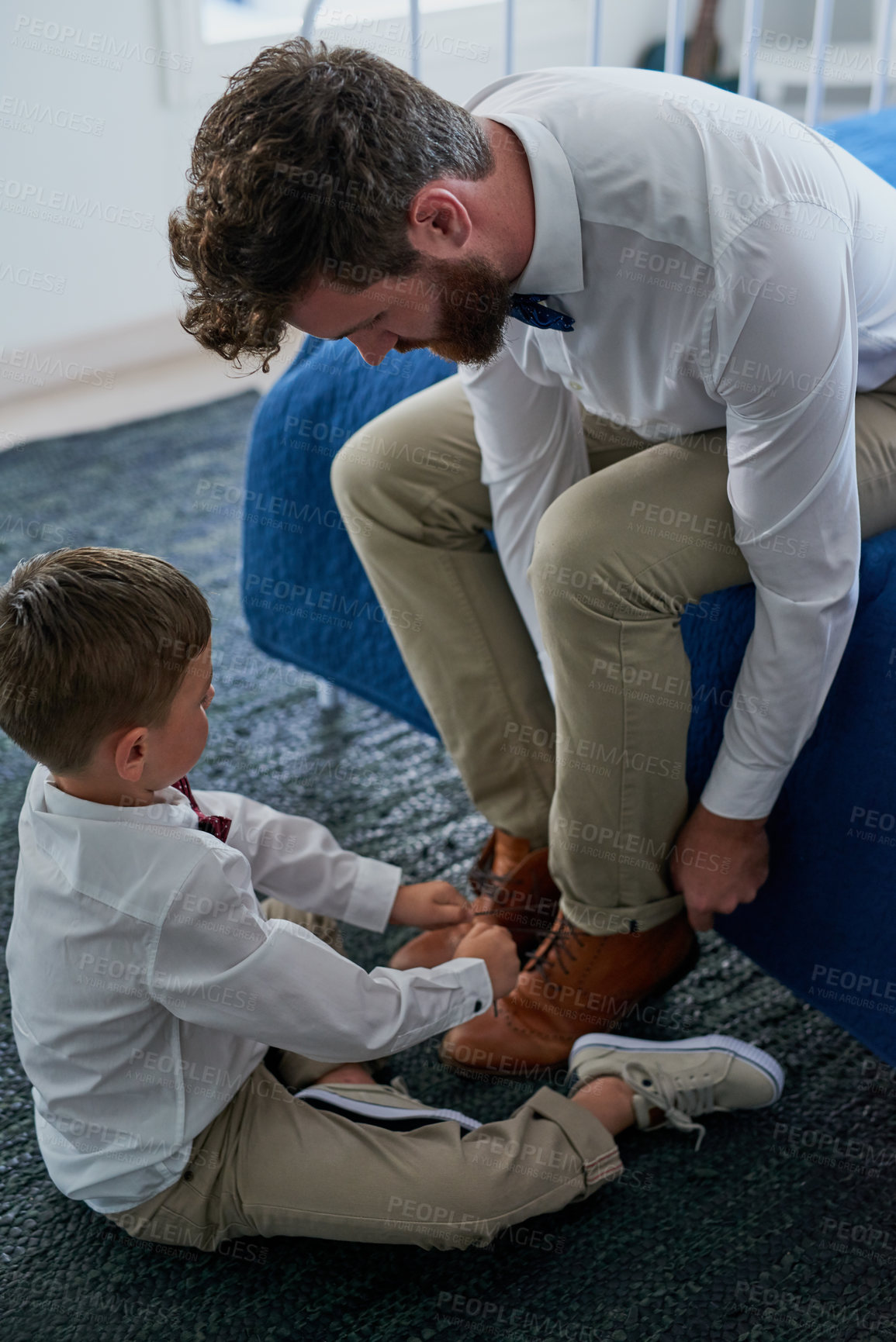 Buy stock photo Cropped shot of an adorable little boy tying his fathers shoelaces at home