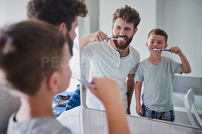 Buy stock photo Shot of a father and his little son brushing their teeth together in the bathroom at home
