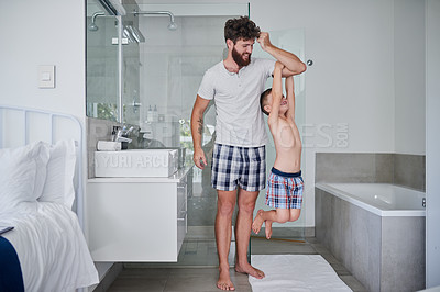Buy stock photo Shot of a little boy hanging on his father's arm in the bathroom at home