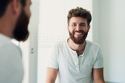 Buy stock photo Cropped shot of a handsome young man looking in the bathroom mirror