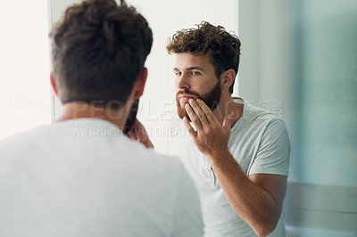 Buy stock photo Cropped shot of a handsome young man checking out his skin in the bathroom mirror