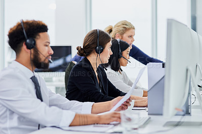 Buy stock photo High angle shot of a team of young people using a computer together in a call center