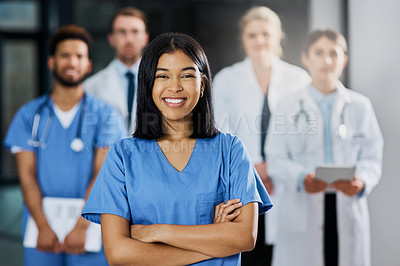 Buy stock photo Portrait of a young nurse standing in a hospital with her colleagues in the background