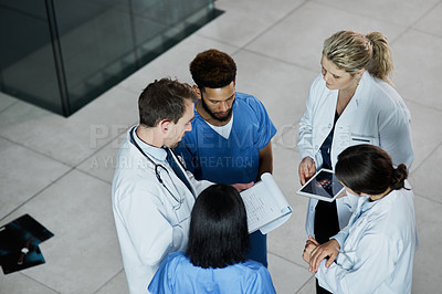 Buy stock photo Shot of a group of medical practitioners having a discussion in a hospital