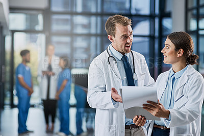 Buy stock photo Shot of two medical practitioners going through paperwork in a hospital