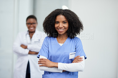 Buy stock photo Portrait of a young nurse standing in a hospital with her colleague in the background