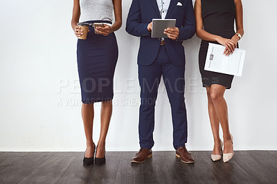 Buy stock photo Cropped studio shot of a group of young businesspeople standing in line against a gray background