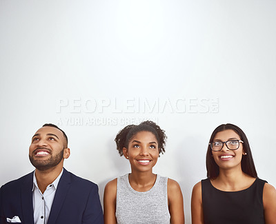 Buy stock photo Studio shot of a group of young businesspeople standing in line and looking up against a gray background