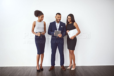 Buy stock photo Studio shot of a group of young businesspeople using a digital tablet together against a gray background