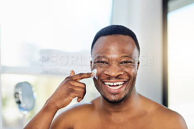 Buy stock photo Portrait of a cheerful young male applying moisturizer to his face during his morning grooming routine