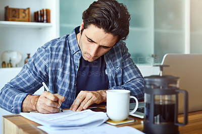 Buy stock photo Shot of a focused young man writing on a document while being seated behind his laptop at home