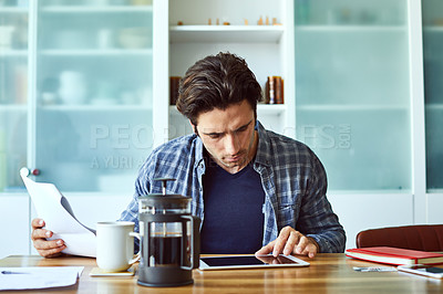 Buy stock photo Shot of a focused young man working on his digital tablet while being seated next to a table at home