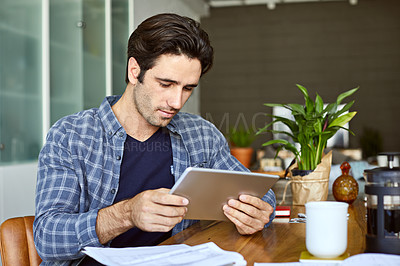 Buy stock photo Cropped shot of a handsome young man using a tablet while working from home