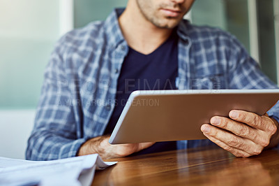 Buy stock photo Cropped shot of an unrecognizable man using a tablet while working from home