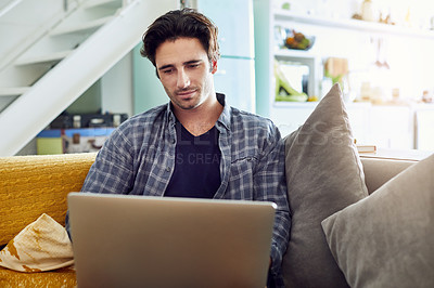 Buy stock photo Shot of a focused young man working on a laptop while being seated on a couch at home