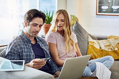 Buy stock photo Shot of a focused young couple working together on a laptop while being seated on a couch at home