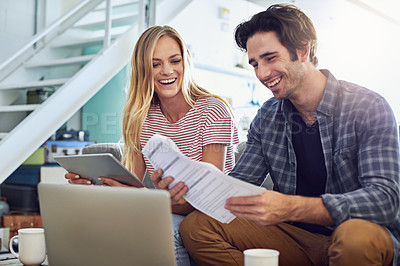 Buy stock photo Shot of a cheerful young couple working together on a digital tablet while being seated on a couch at home