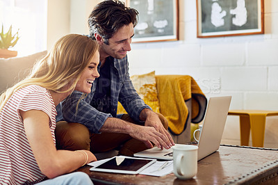 Buy stock photo Shot of a cheerful young couple working together on a laptop while being seated on a couch at home