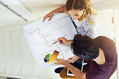 Buy stock photo High angle shot of a focused young couple drawing plans and choosing colors for the renovation of their house