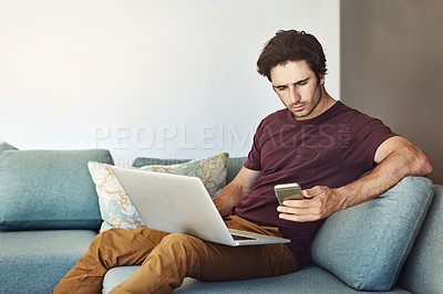 Buy stock photo Shot of a handsome young man using his laptop and mobile phone on the sofa at home