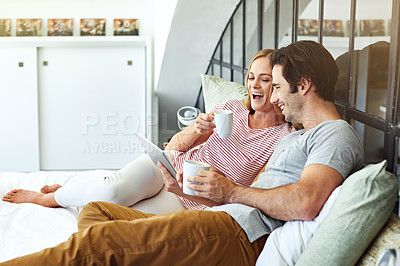 Buy stock photo Shot of a young couple using a digital tablet together while relaxing on the sofa at home