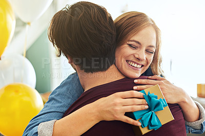 Buy stock photo Shot of a young couple exchanging gifts at home
