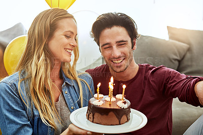 Buy stock photo Shot of a young couple having cake while celebrating a birthday at home
