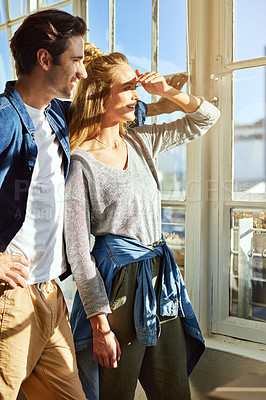 Buy stock photo Shot of a young couple looking out of the window at home