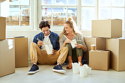 Buy stock photo Shot of a young couple eating takeout while taking a break moving into their new home