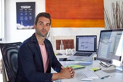 Buy stock photo Shot of a handsome young man sitting in his office