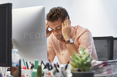 Buy stock photo Shot of a businessman looking exhausted while sitting at his desk
