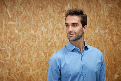Buy stock photo Cropped shot of a handsome young man posing against a wooden wall
