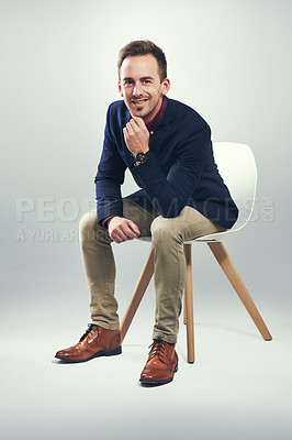 Buy stock photo Studio portrait of a confident young businessman sitting on a chair against a gray background