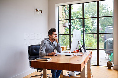 Buy stock photo Shot of a young man using a computer while working from home