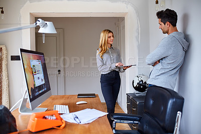 Buy stock photo Shot of a young couple working together in their home office
