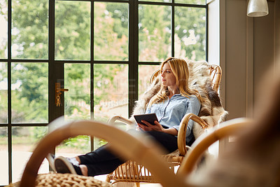 Buy stock photo Shot of a young woman using a digital tablet while relaxing on a rocking chair at home