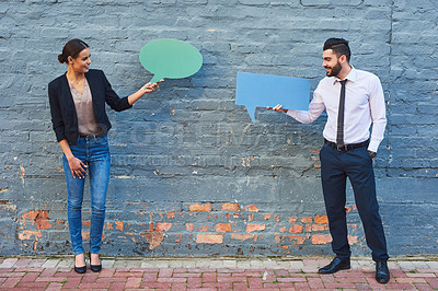 Buy stock photo Shot of two businesspeople holding speech bubbles against a brick wall outdoors