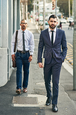 Buy stock photo Portrait of two businessmen walking in the city