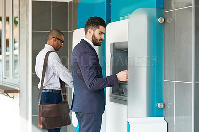 Buy stock photo Shot of two businessmen making transactions at an ATM